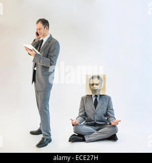 Businessman imagining self image of meditating while multitasking - Stock Photo
