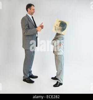 Businessman showing thumbs up to boy wearing mask - Stock Photo
