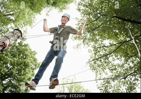 Portrait of mature man climbing crag, smiling - Stock Photo