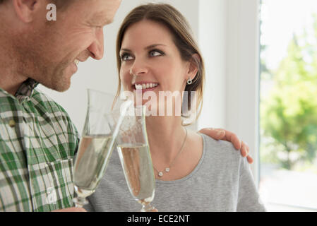 Couple celebrating drinking toasting new home - Stock Photo