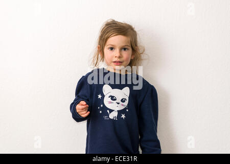 Portrait, three-year-old girl with fair hair, blue sweater with the picture of a white cat - Stock Photo