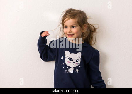 Portrait, smiling three-year-old girl with fair hair, blue sweater with the picture of a white cat - Stock Photo