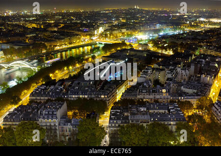Paris by night, river Seine reflecting city lights and buildings glow under street lamps - Stock Photo