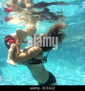 Mother kissing baby boy underwater in a swimming pool - Stock Photo