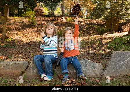 Boys (2-5) having fun in autumn park - Stock Photo