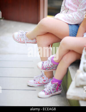 Argentina, Buenos Aires, Sisters sitting cross-legged side by side - Stock Photo