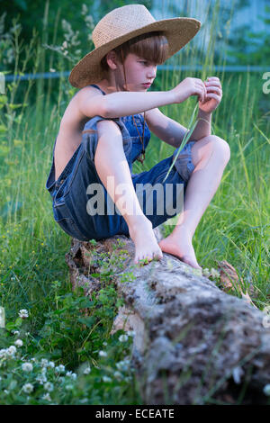 Young boy wearing blue overalls sitting on fallen tree - Stock Photo
