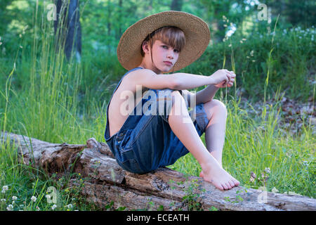 Young boy sitting on log wearing straw hat and blue overalls - Stock Photo