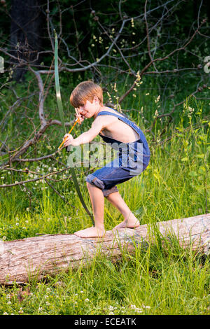 Young boy on fallen tree with bow and arrow - Stock Photo
