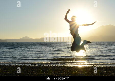 USA, Washington State, Olympic National Park, Action shot of silhouette of woman jumping on beach at sunset - Stock Photo