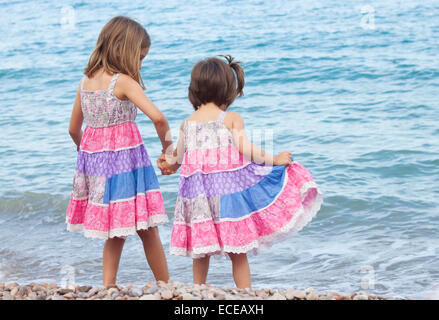 Two sisters standing on beach holding hands - Stock Photo