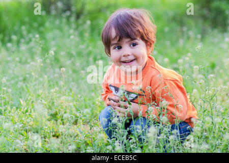 Boy (2-3) in grass - Stock Photo