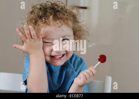 Happy girl eating a lollipop and touching her face - Stock Photo