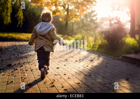 Boy running towards rising sun - Stock Photo