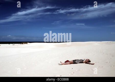 Spain, Canary Islands, Fuerteventura, Nature Park of Dunes of Corralejo, Woman lying in desert - Stock Photo