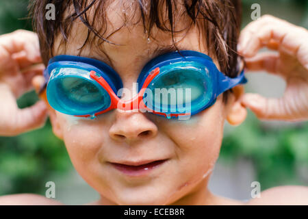 Portrait of boy (4-5) wearing swimming goggles - Stock Photo