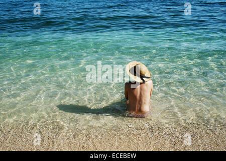Croatia, Krk Island, Stara Baska boot topping, Woman sitting in water - Stock Photo