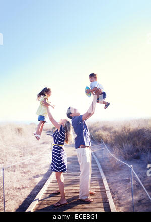 Parents holding kids in air - Stock Photo