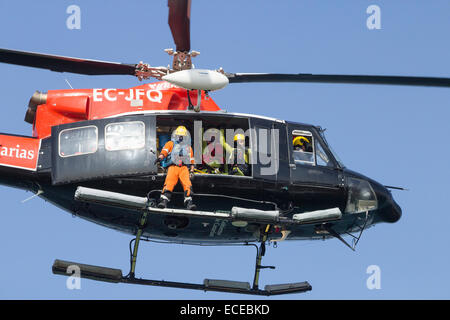 Spanish coastguard helicopter taking part in rescue services simulation on beach in Spain - Stock Photo