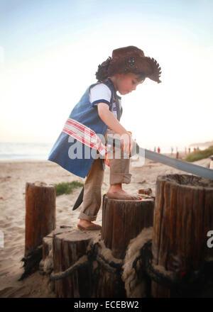 Boy in pirate costume on beach - Stock Photo