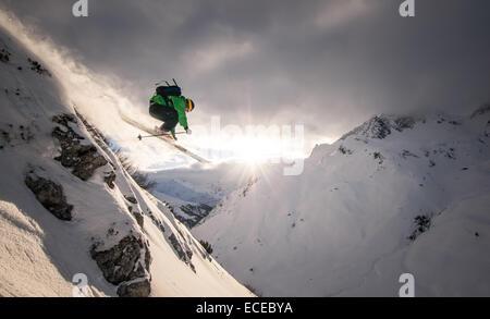 Austria, Freeride skier jumping off rock - Stock Photo