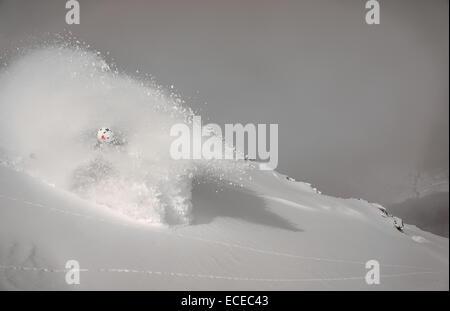 Austria, Salzburg, Gastein, Skier descending slope in cloud of powder snow - Stock Photo