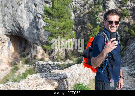 Man taking picture with mobile phone in mountains, Tarragona, Catalonia, Spain - Stock Photo