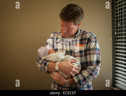 Father holding newborn baby in hospital - Stock Photo