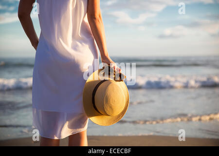 Rear view of woman in white dress standing on beach and holding hat - Stock Photo