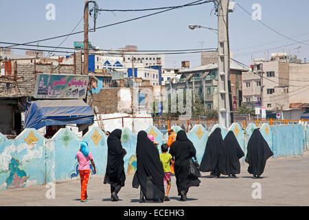 Iranian women, dressed in black burqas / burkhas, walking in street with children in the city Mashhad, Razavi Khorasan, - Stock Photo