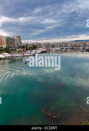 Sunken fishing boat below water, abandoned in port of Zea Marina in Greece with passing fishing boat returning in - Stock Photo