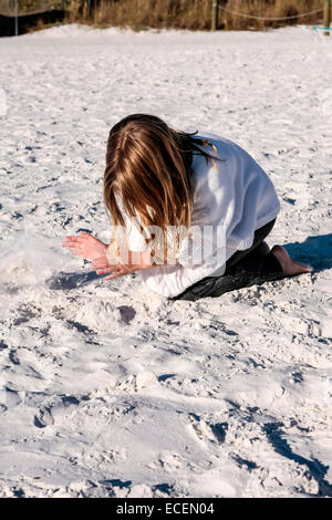 A young pre-teen girl playing in the sanss of Siesta Key beach FL on a cold November day - Stock Photo