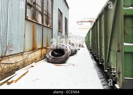 reinforcement rolls near warehouse on railroad station in winter - Stock Photo