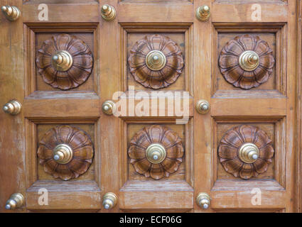 Ornate carved wood and brass design on a temple door - Stock Photo