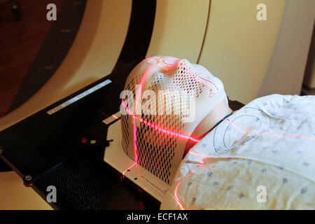 Lasers are used to position a patient model wearing a short face mask in a computed tomography (CT) scanner to obtain - Stock Photo