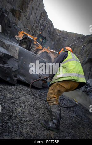 Quarryman Dave Cowerd splits some Kirkby Stone at Burlington Slate ltd in Cumbria, England, United Kingdom. - Stock Photo