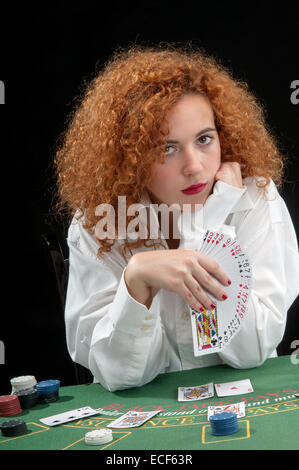 young woman croupier at the green table, while dealing the cards - Stock Photo