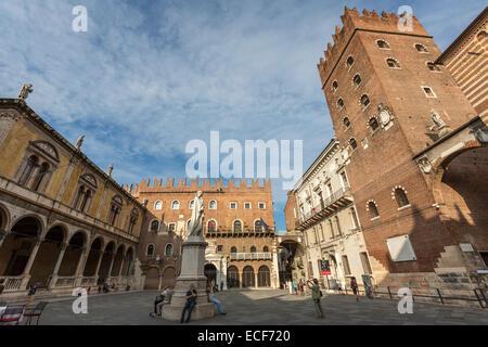 The statue of Dante in Piazza dei Signori, also known as Piazza Dante, and the Palace Cansignorio - Stock Photo