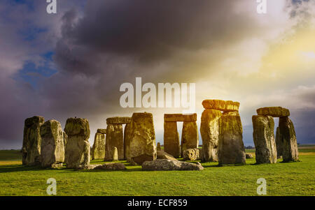 Stonehenge, prehistoric monument, set against a foreboding sky and a blue sunny at Amesbury, Wiltshire, UK.hire, - Stock Photo
