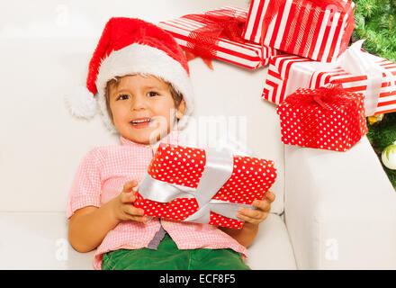 Happy little boy in Christmas cap holding presents and big smile on the sofa near New year tree wearing Santa Claus - Stock Photo