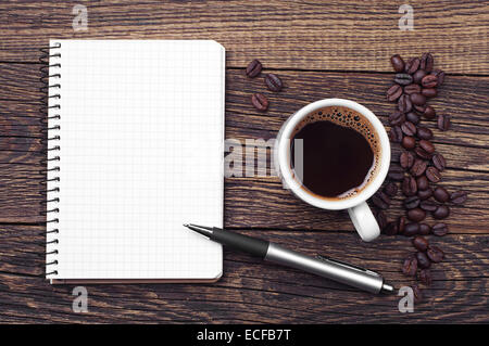Notepad, pen and cup of coffee on vintage wooden table. Top view - Stock Photo