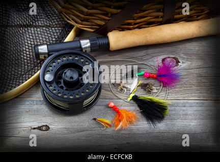 Close up top view of  fishing fly reel, landing net, creel and assorted flies, partial cork handled pole on rustic - Stock Photo