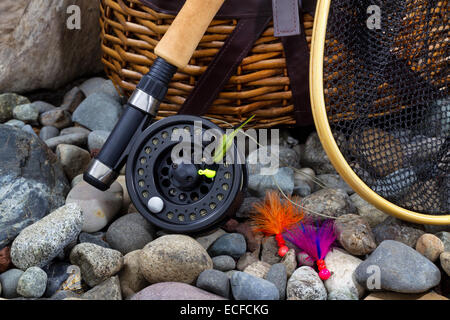 Close up of  fishing fly reel, landing net, creel and assorted flies on dry river bed rocks - Stock Photo