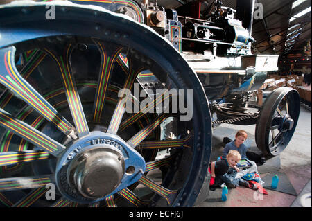 Two young brothers sit under the giant decorative wheels of Traction Engine 'The Champion' built by Ruston Proctor - Stock Photo