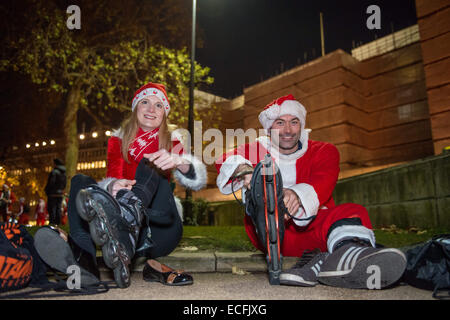 London, UK. 13th December, 2014. Hundreds of roller blading Santas from the weekly London Skate took to the streets - Stock Photo