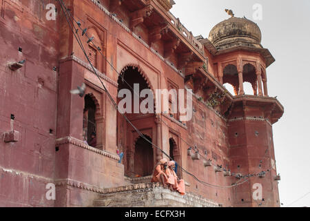 Two Babas in traditional orange robes sit on the steps of a Hindu temple in Varanasi.  Pigeons fly overhead in the - Stock Photo