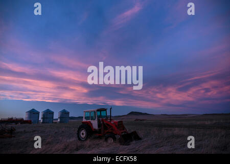 Farm equipment on the Southern Alberta prairies near Cowley at dusk.  A storm approaches over the Livingstone Range - Stock Photo