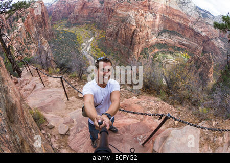 young caucasian man taking a selfie over the steep cliffs of the  Angels Landing hiking trail in Zion NP - Stock Photo