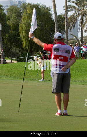 Dubai. 13th Dec, 2014. Melissa Reid of England's caddy waits to take the flag out of the hole while she putts during - Stock Photo