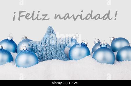 spanish Christmas card with blue christmas balls and text merry christmas - Stock Photo